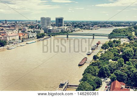 Bridges over the Danube river in Bratislava city Slovak republic. Docks scene. Old bridge and Apollo bridge. Ship transportation. Retro photo filter. Travel destination.