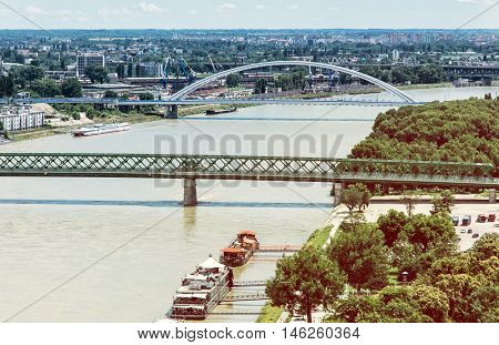 Bridges over the Danube river in Bratislava city Slovak republic. Old bridge and Apollo bridge. Ship transportation. Gradient photo filter. Capital city of Slovakia. Travel destination.
