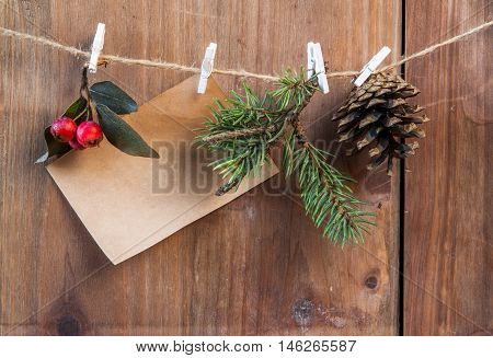 Note, Christmas tree branch, pine cone and winter berries on a rope with clothespins. Wishing a merry Christmas
