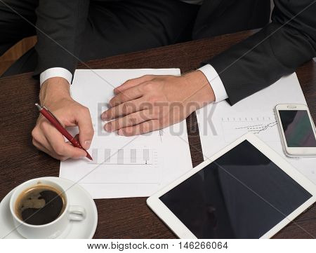 Businessman writing on the paper next to the tablet, coffee, cell phone.