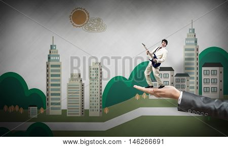 Big female palm on holding small confident businessman playing guitar
