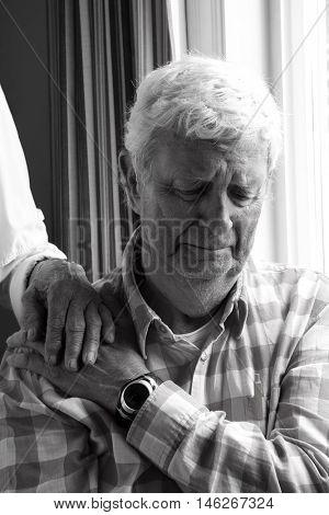 Senior gentleman age 78, sad and holding his wife's hand.