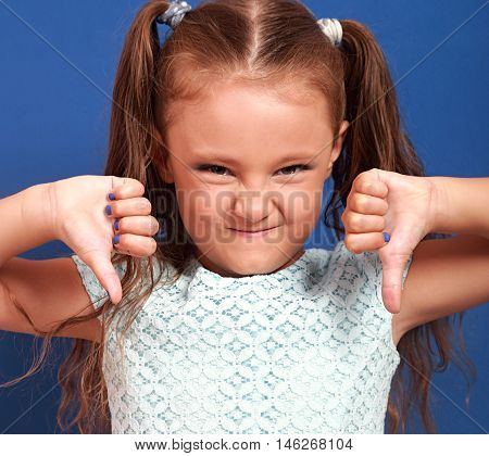 Fun Grimacing Kid Girl Showing Thumb Down On Blue Background. Closeup Emotional Portrait