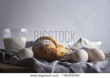 Still life of croissants, eggs, milk and flour. Rustic style.
