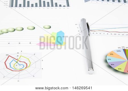 Business still-life of shiny pen, sticker, bookmarks, graphs