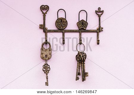 brass antique skeleton keys hanging on pink wall