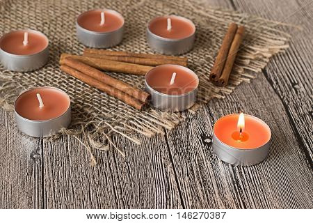 Cinnamon sticks and decorative candle with aroma of cinnamon on sackcloth on gray wooden table.