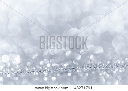 Abstract background with silver shiny glitter bokeh lights
