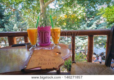 SPILI, CRETE, GREECE - JULY 2016: Orage juice glasses and menu card on table at traditional Greek taverna on Crete island