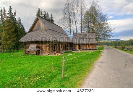 Country road and wooden huts in beautiful mountain valley in Western Tatra Poland.