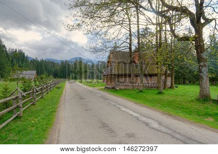 Country road and wooden hut in beautiful mountain valley in Western Tatra Poland.
