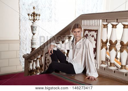 Beautiful man in the clothing of the 18th century in a interior with stairs