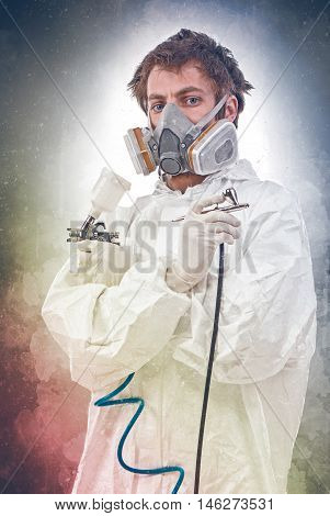 Worker with airbrush gun on a colored background