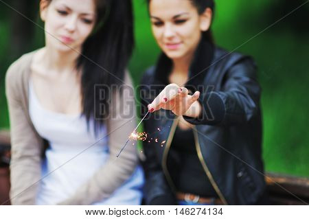 Portrait Of Happy Young Women Friends Laughing And Holding Sparklers In Outdoors. Friendship And Cel