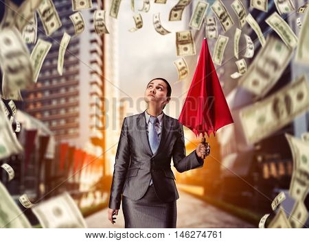 Businesswoman with umbrella in money rain