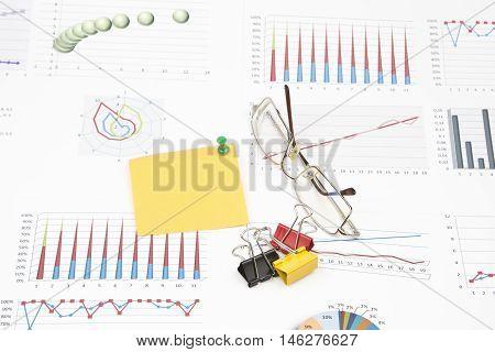 Business still-life of sticker, graphs, eyeglasses, pushpin, paperclip