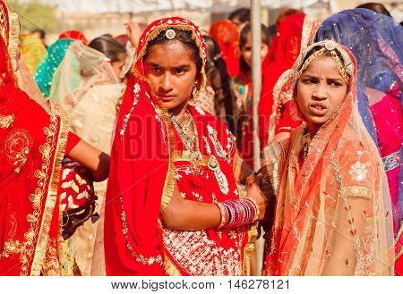 JAISALMER, INDIA - MARCH 1, 2015: Beautiful indian girls posing serious in traditional sari dresses in colorful crowd on the Desert Festival on March 1, 2015. Every winter Jaisalmer takes Desert Festival
