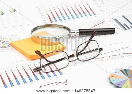 Business still-life of a sticker, eyeglasses, magnifier