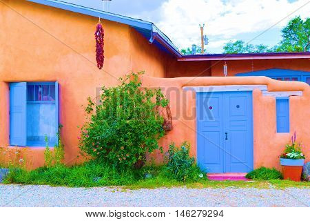 Southwestern adobe style home with a garden and hanging red chile peppers taken in Taos, NM