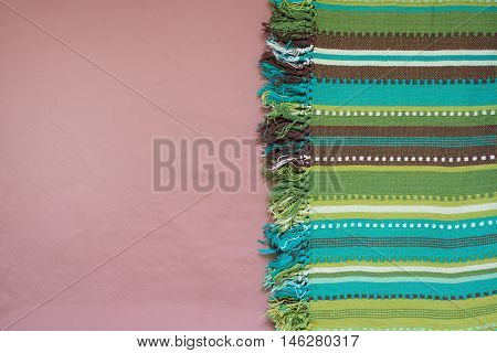 Pink background and striped cotton fabric green tones on the edge. Copy space.