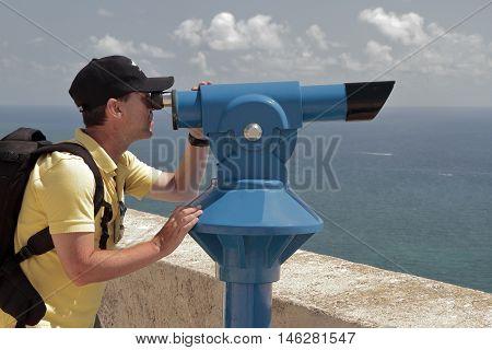 man using a panoramic telescope looking at the Mediterranean sea