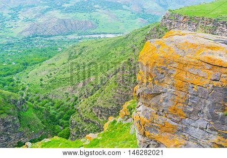 The boulders and rocks in mountain village of Saro covered with bright yellow and orange lichen Georgia.