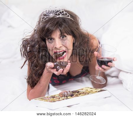 Upset Woman In Tiara Drinking Wine And Gulipng Down Chocolates In Bedroom