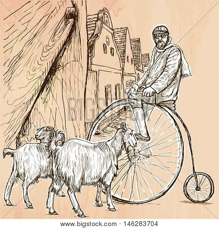 BICYCLIST. Cyclist on the velocipede posing at the old village. In front of old houses are also two goats. Freehand sketching line drawing. An hand drawn vector illustration. Line art technique.