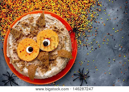 Owl cake. Halloween or birthday party dessert delicious cream cake in the form of an funny owl. Halloween cake on a festive decorated table creative idea for treats