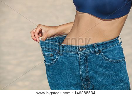 A young girl wears jeans that become large after weight loss and diet. Reducing excess weight. Healthy lifestyle.