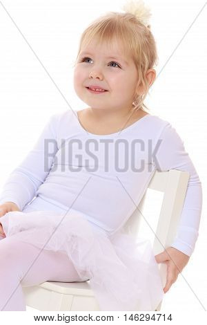 Happy little girl , a future figure skater, sits on a chair in a White sports dress , close-up-Isolated on white background