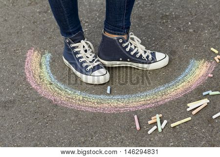 Feet in sneakers are on the pavement next to the picture of the Rainbow
