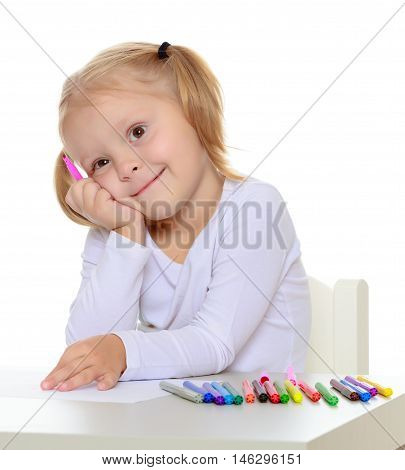 Pretty little blonde girl drawing with markers at the table.Girl put head on his hand , she dreams about something.Isolated on white background