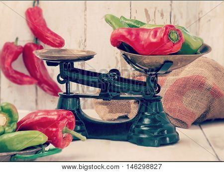 authentic country farmhouse scene showing freshly picked organic green and red peppers in green scales on an old wooden table. Instagram style filter added soft window light. copy space.