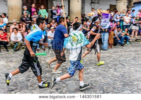 Antigua Guatemala - September 14 2015: Locals run in streets with lit torches & flags draped around them & blow whistles during Guatemalan Independence Day celebrations