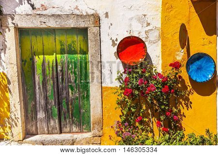 White Yellow Wall Green Door Orange Blue Bowls Red Roses Street 11th Century Medieval Town Obidos Portugal.