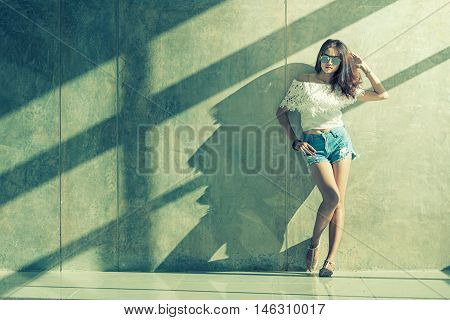 Fashion Portrait Of Young Model Posing By The Wall