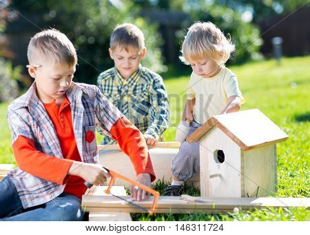 Happy kids boys brothers making wooden birdhouse by hands