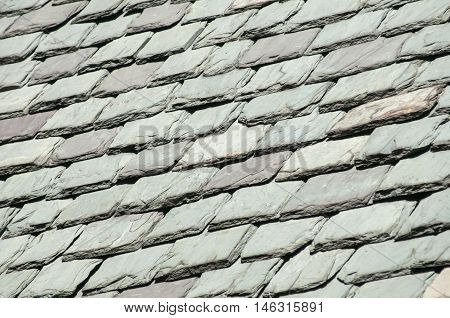 Old grey stone tiles on old vintage house roof as background