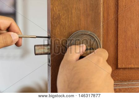 locksmith on wood door for reparing by screwdriver