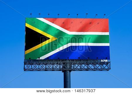 south africa flag on billbroad advertise and blue sky background - can use to promote or montage on your product