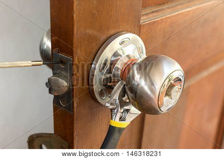 locksmith on wood door with screwdriver for repair or fix silver knob vintage texture - can use to web template about home service