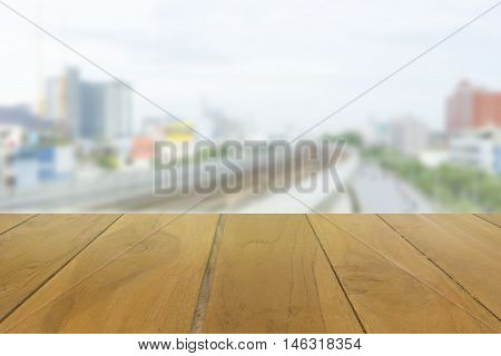 wood table top on blur railway and road background - can use to display or montage on product