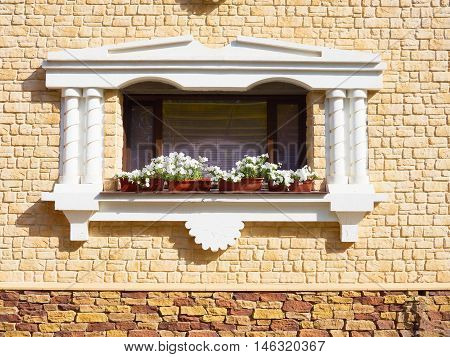 White flowers hangs on the window of a home in an ancient building surrounded by beautiful patterns in the stone wall.