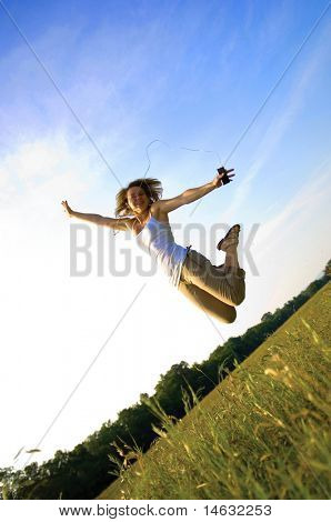 teenage girl listening to portable music player leaping in the air
