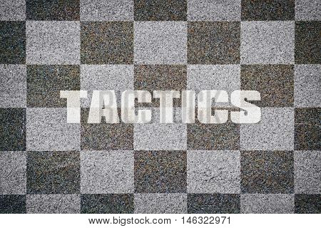 Word Tactics written on textured chessboard as background