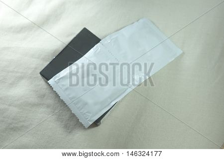 Condom with silver condom packages on bed