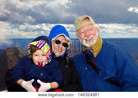 Happy grandparents hold their young granddaughter at the overlook of Bright Angel at the North Rim of the Grand Canyon. All three are dressed in winter clothes and snow is falling around them.