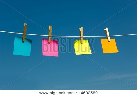 Colored sticky notes on a clothesline with a blue sky background