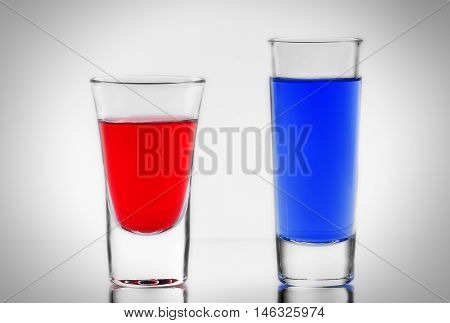 the two blue and red cocktail in full transparent shot glasses with own reflections